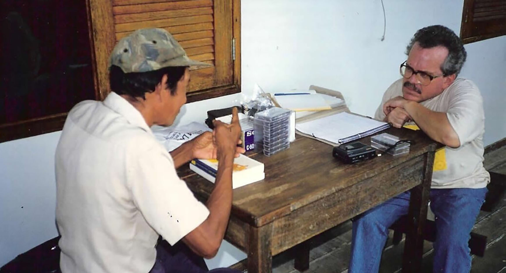 two men having a discussion at a wooden table with audio cassettes and notebooks on it.