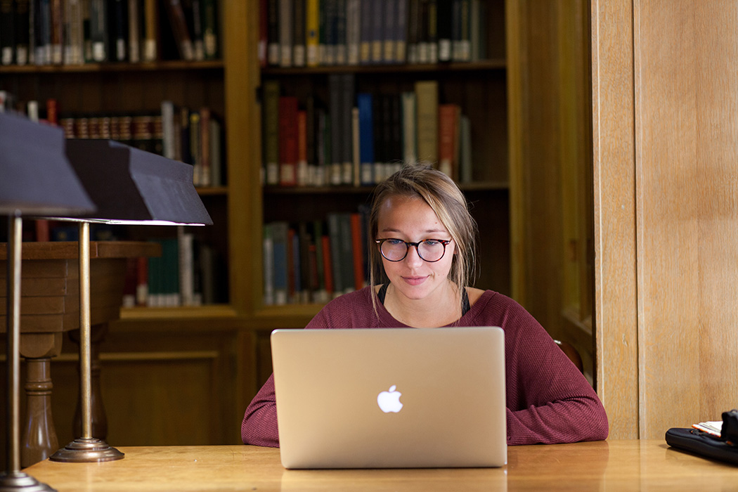 college student in glasses smiles while viewing laptop screen, books in background