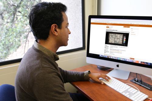 man viewing website on desktop computer