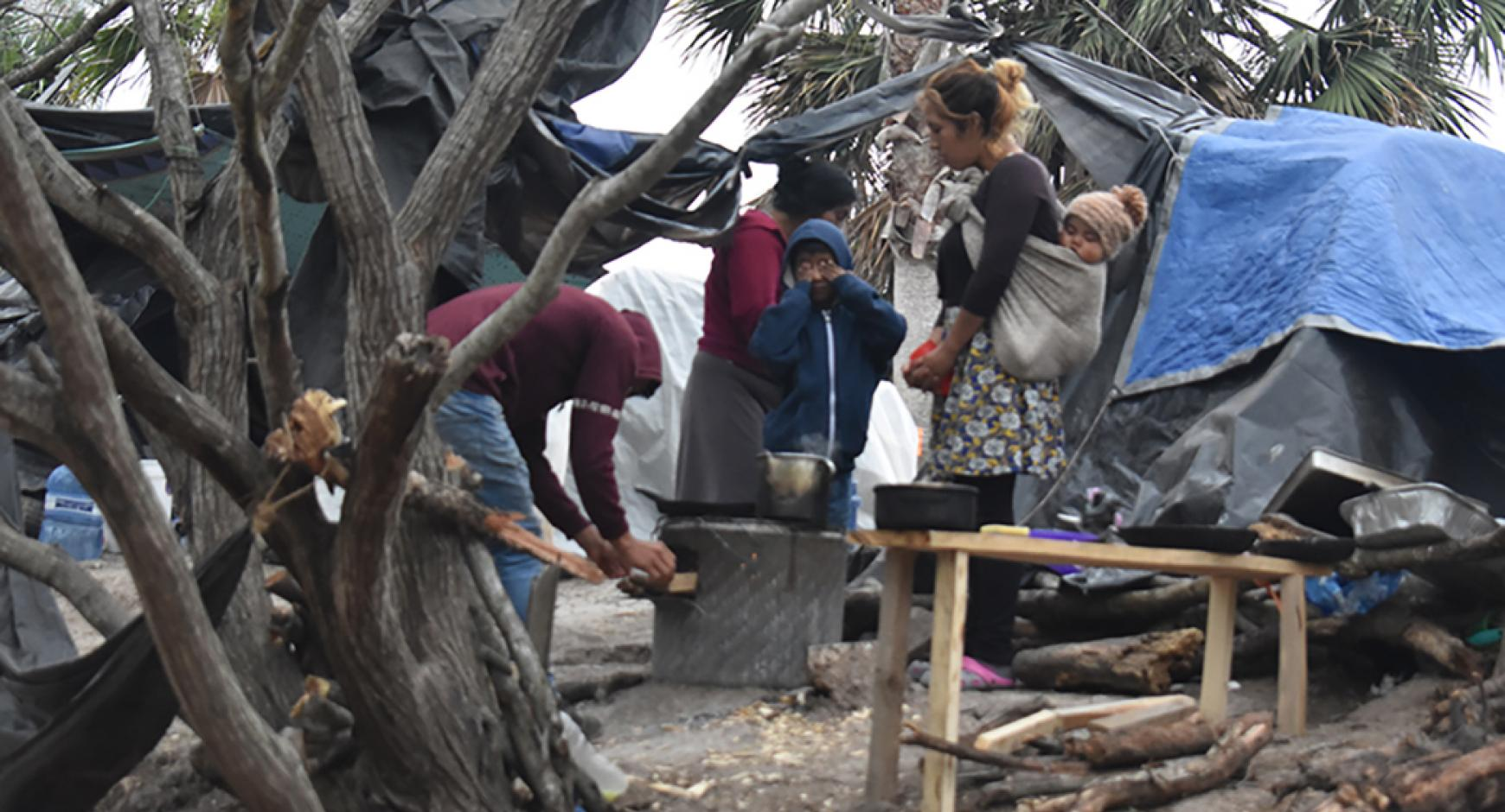 woman with child in refugee camp surrounded by tents and working men