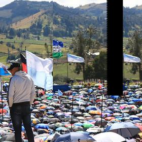Man standing above field of umbrellas at rally. Feature image taken in Boyacá, Colombia, by Sofia Mock.