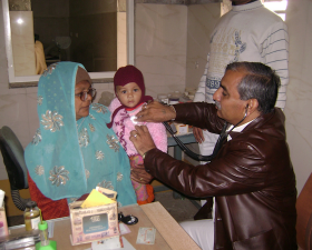 man holding stethoscope to baby being held by woman