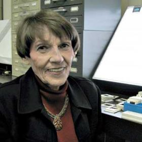 woman wearing black blazer smiles at camera