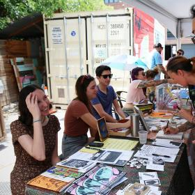 people standing on either side of tables looking at zines
