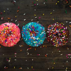 three donuts with sprinkles on a table