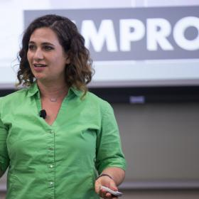 woman in green shirt gestures while speaking