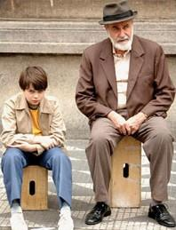 a boy and an older man sit on boxes on the street