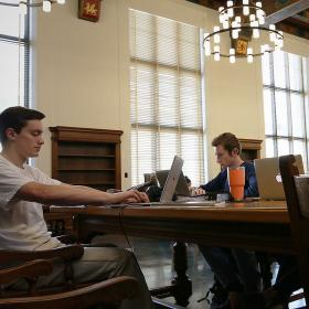 three students study at table in historic room