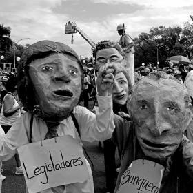 Two men wearing paper-mache masks and signs around their necks