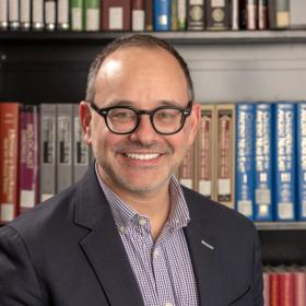 man in black framed glasses smiles at camera in front of bookself
