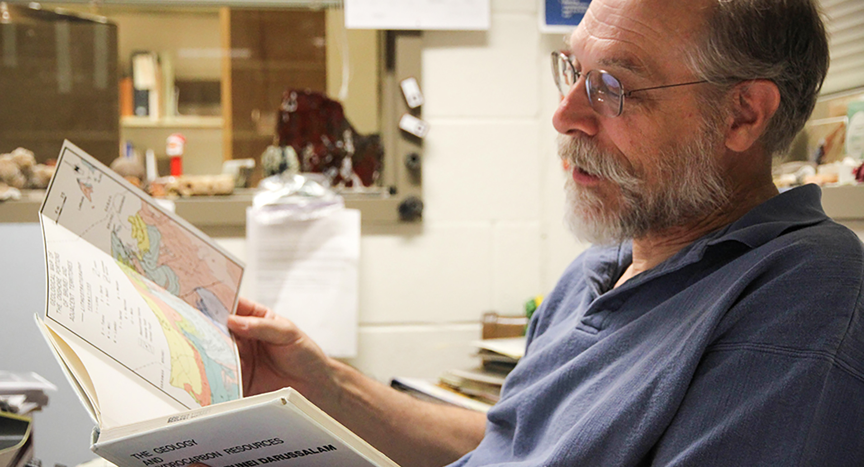 man in beard and blue polo sitting at desk reading book in profile